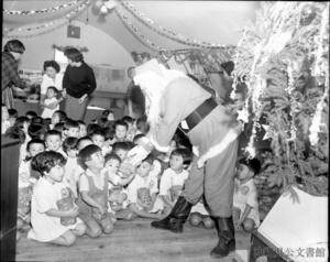 沖縄を統治していた琉球列島米国民政府(USCAR)の広報写真。米国と沖縄の国際親善を目的にした「婦人クラブ」のクリスマスパーティーで、サンタクロースからキャンディーの箱をプレゼントされる保育園の子どもたち=1963年12月16日、沖縄県公文書館所蔵