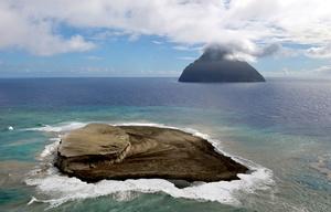 波に浸食される福徳岡ノ場の新島。奥は南硫黄島=2021年10月15日午後、東京・小笠原諸島、朝日新聞社機から、恵原弘太郎撮影