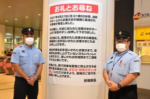 転落事故の救助活動へのお礼などが書かれた張り出しと野田一洋駅長(左)、彌榮俊介助役=2021年10月12日、北九州市八幡西区