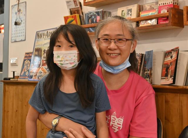 環境保護のため、石灰礁の保護を求める住民投票の署名集めに加わった黄婷婷さん(右)と長女=2021年9月、台湾北部の桃園市、石田耕一郎撮影