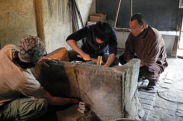 樂家の窯場で。黒窯の翌日に、16代の長男篤人さん(中央)、彫刻家の次男雅臣さん(左)と窯を修復する=田口葉子氏撮影