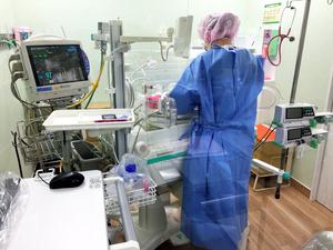 新型コロナウイルスに感染した妊婦から生まれた新生児の様子を見る看護師=さいたま市立病院提供