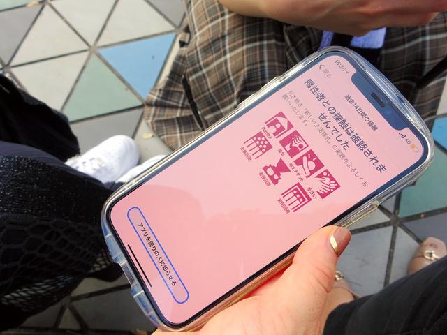 ライブ会場で入場を待つ女性がココアを開くと、「陽性者との接触は確認されませんでした」と表示された=2021年10月、東京都内、平井恵美撮影