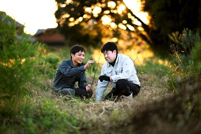 自宅裏の畑に植えた誕生日プレゼントの木を見つめる加納克典さん(右)と嶋田全宏さん。今後も記念日には木を植えていくつもりで、数十年先の畑の様子を楽しみにしている=2021年10月15日午後、三重県伊賀市、白井伸洋撮影