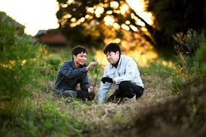 自宅裏の畑に植えた誕生日プレゼントの木を見つめる2人。今後も記念日には木を植えていくつもりで、数十年先の畑の様子を楽しみにしている=2021年10月15日午後、三重県伊賀市、白井伸洋撮影