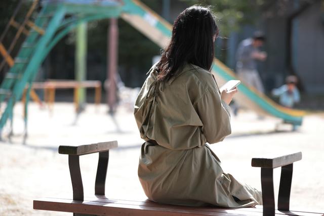 公園のベンチでスマホを手にする女性。今も家族のことは誰にも話していない=2021年10月24日午前、愛知県内、山本正樹撮影