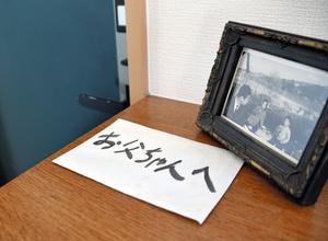 孤独死したときのために男性は「遺言」を玄関に置いている。楽しかりし子どものころの家族写真をそばに=2021年10月22日、和歌山市、下地毅撮影