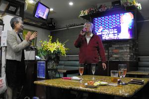 酒でのどを潤し、マイクを握る男性客=2021年10月25日午後6時16分、千葉市中央区弁天2丁目、高室杏子撮影