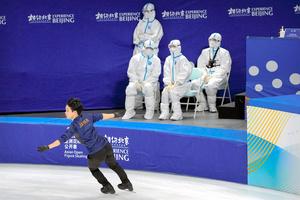 北京の首都体育館で2021年10月13日、フィギュアスケートの冬季五輪テスト大会の練習をする鍵山優真選手。防護服姿の医療従事者の前を滑った=AP