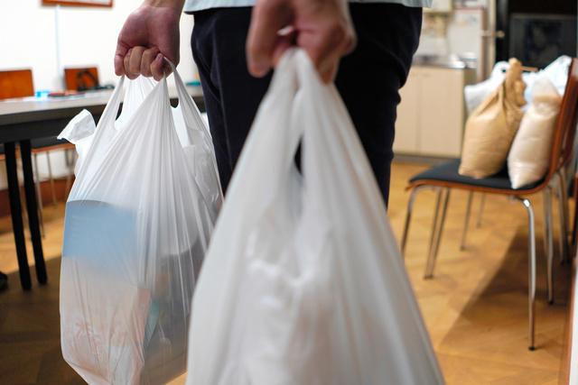 「ぼたんこども食堂」の食料支援に訪れた大学生。両手に持つ袋には、たくさんの食料が詰められていた=2021年10月8日、東京都江東区、藤原伸雄撮影