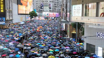 雨のなか銅鑼湾地区の繁華街を歩くデモ参加者ら=2019年8月18日、香港、西本秀撮影