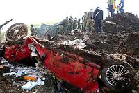 土砂崩れの現場で捜索する自衛隊員たち。近くには土砂に埋もれた乗用車があった=19日午前8時53分、熊本県南阿蘇村の高野台地区、上田潤撮影