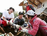 地震の被害にあった自宅付近で、土砂の中から思い出の品を見つけ笑顔を見せた=19日午後1時43分、熊本県南阿蘇村の高野台地区、上田潤撮影