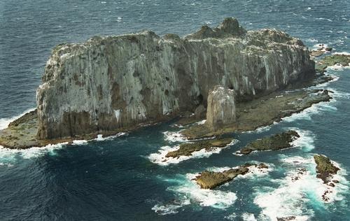 尖閣諸島のなかで最も沖縄本島寄りにある大正島(赤尾嶼)。最も高いところが82メートル、面積4ヘクタールの長く切り立った岩場の島は、米軍の射爆場だった。断がいには今も砲弾の跡があちらこちらに残る。島影が艦船に見立てやすいことも理由だった=2001年4月、朝日新聞社ヘリから
